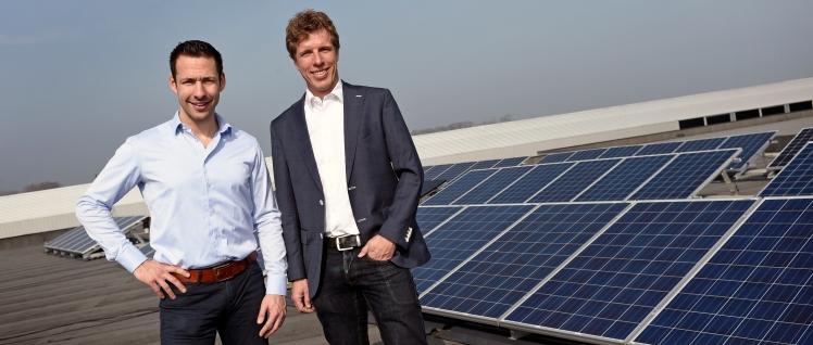 Marcel Blaauw en Bart Mossink van Zonnepanelen.net bij de zonnepanelen op het dak van hun pand in Ede